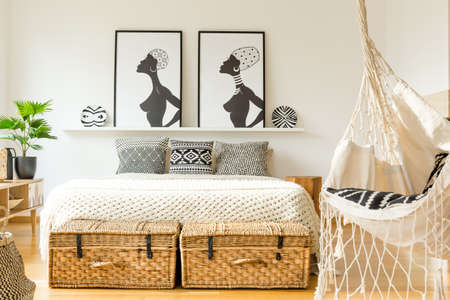 Swing in a rustic bedroom interior with king size bed, graphics, plant and straw baskets Stock Photo
