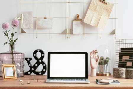Laptop with mock-up screen, golden frame notes organizer and creative decorations on a wooden desk in a hipster work space interior