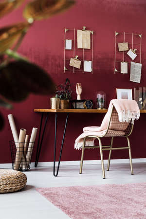Blanket on gold chair at wooden desk with clock in feminine, pink home office interior