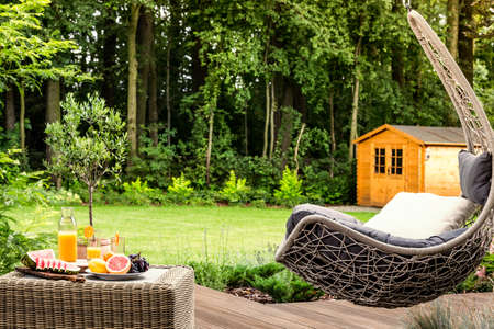 Pillow on hanging chair next to a table with grapefruit and orange juice on wooden patio in the garden