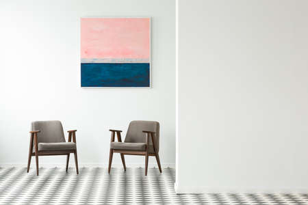 Pastel painting on white wall above grey armchairs in interior with checkerboard floor Stock Photo
