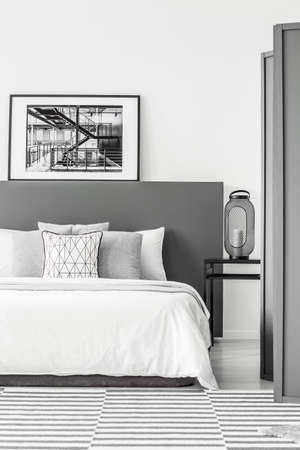 Black and white poster on bedhead of bed in simple bedroom interior with lantern on a bedside table
