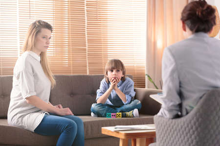 Boy with autism and his worried mother during consultation with therapist