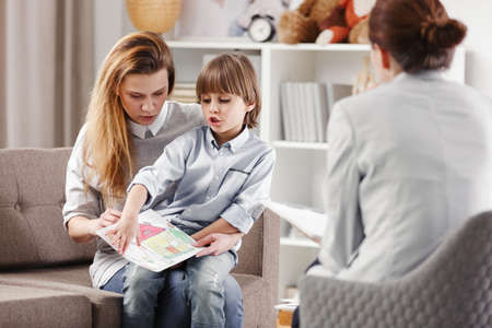 Mother with autistic child holding a drawing during consultation with psychotherapist