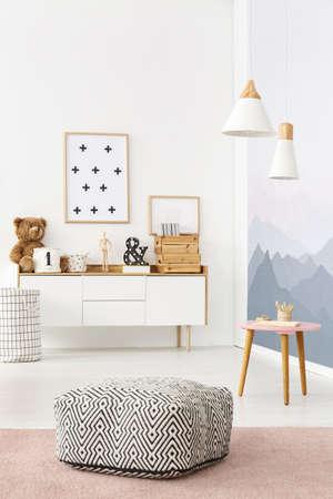 puf blanco y negro con el patrón colocado en interiores brillante habitación con carteles y decoraciones en armario de madera