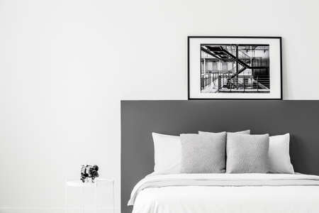 White bed with black bedhead in contrast bedroom interior with poster and copy space 写真素材