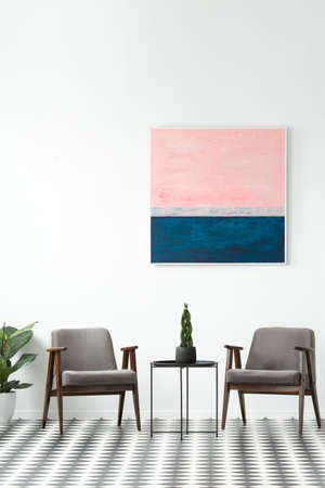 Plant on a table between grey armchairs in modern interior with pink and blue painting on white wall Stock Photo