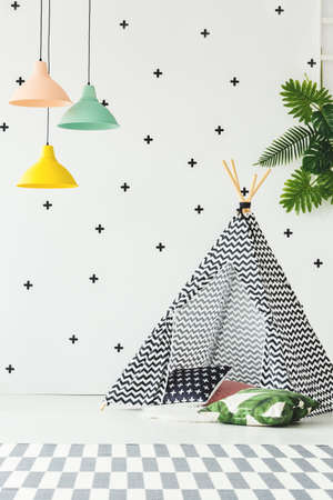 Yellow, peach and green lamp above patterned carpet in playroom interior with tent and pillows Stock Photo