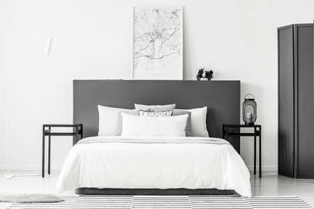 Poster on black bedhead in minimal hotel room interior with white bedsheets on bed