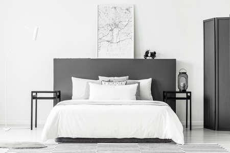 Plakat auf schwarzem Bettkopf im minimalen Hotelzimmerinnenraum mit weißen Bettlaken auf Bett