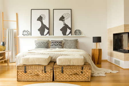 African posters, wicker boxes, fireplace and double bed with patterned pillows in a boho bedroom interior