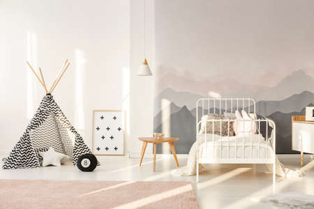 Patterned teepee standing in bright kids room interior with white bed, mountain wallpaper and powder pink carpet Stockfoto