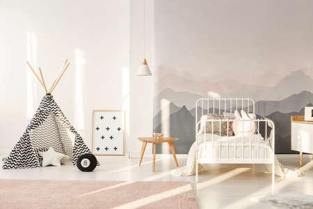 Tipi estampado de pie en el interior luminoso de la habitación de los niños con cama blanca, papel tapiz de montaña y alfombra rosa empolvado