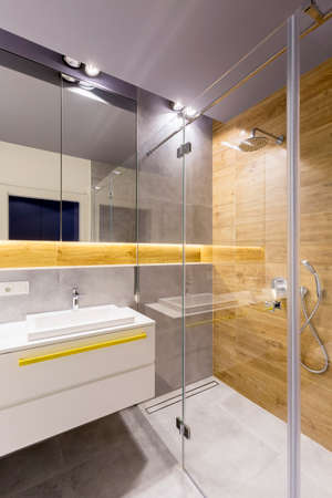 Modern bathroom interior with glass shower cabin, dark gray tiles, mirror and white washbasin