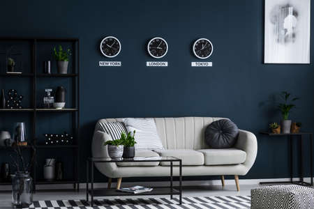 White sofa, coffee table, metal shelf with decorations and three clocks on the blue wall in living room interior