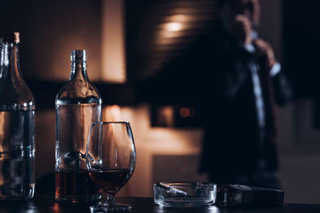 Bottle, glass with alcohol and cigarettes with a businessman in the background Stock Photo