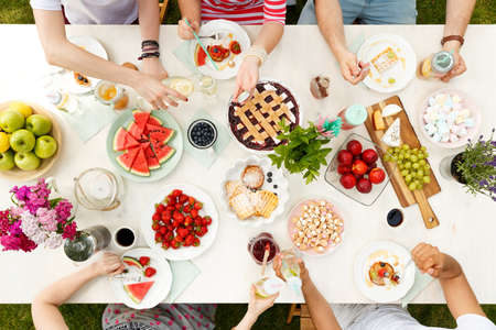 Young students having a meal outside, drinking and eating pie, watermelon, apples and grapes at a table with flowers Stock Photo