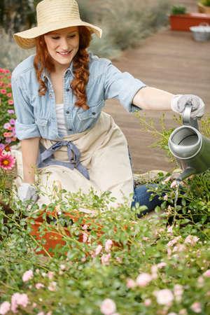 Smiling gardener woman watering flowers in the garden