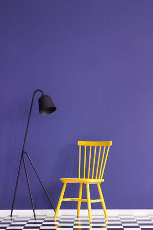 Black lamp next to a yellow chair on checkerboard floor in violet room interior