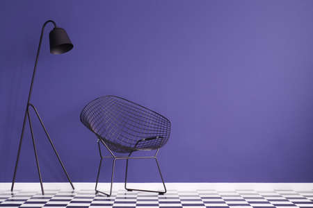 Black lamp next to an armchair on checkerboard floor in violet interior with copy space Standard-Bild - 100062316