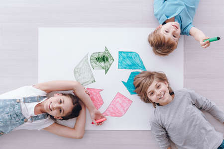 High angle of happy kids drawing colorful recycling symbol during ecology classes 版權商用圖片