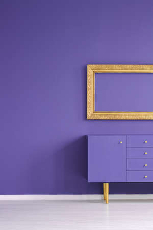Mockup of empty gold frame above violet cabinet in room interior with copy space on the wall