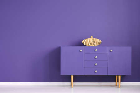 Gold vase on violet cabinet against the wall with copy space in anteroom interior