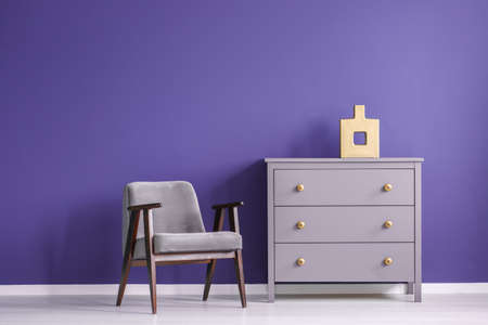 Grey wooden armchair next to a violet cabinet against purple wall in minimal living room interior