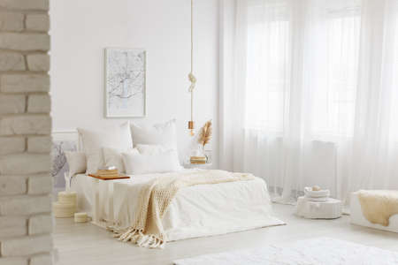 Bed with white bedding in spacious bedroom interior with gold decorations and big window Reklamní fotografie