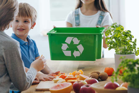 Kids in the kitchen throwing out fruit remains into a green bin for biodegradable waste Banco de Imagens