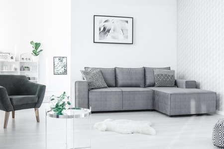 Schwarzweiss-Plakat, das an der Wand im flachen Innenraum des offenen Raums im nordischen Stil mit frischen Pflanzen hängt Standard-Bild