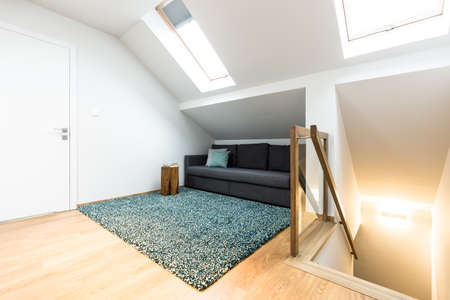 Hidden, grey sofa with cushions in the attic next to stairs and colorful rug