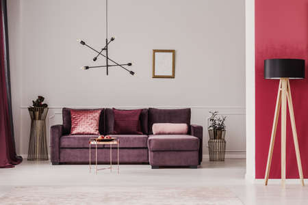 Wooden lamp against red wall in sophisticated living room interior with violet corner couch