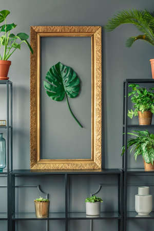 Close-up of an elegant, golden frame with a green monstera leaf standing on a black, metal rack against black wall