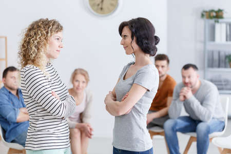 Two happy women making amends during a group psychotherapy meeting