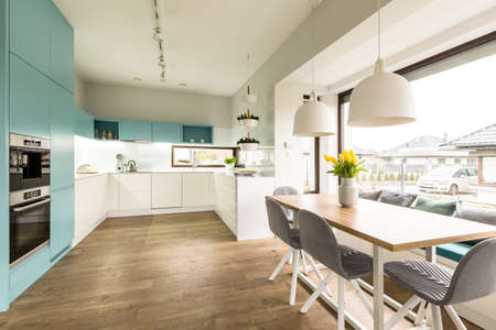 White and blue kitchen interior with big dining table, chairs and window 版權商用圖片