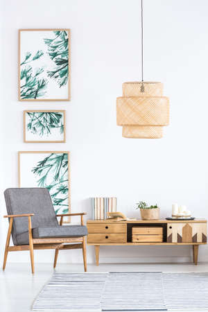 Rattan lamp above wooden cupboard and grey armchair in retro living room interior with leaves posters