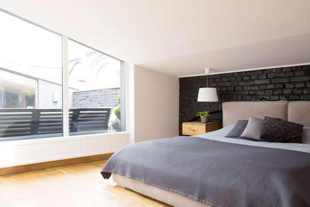 Windows in spacious bedroom interior with grey bedding on bed against black brick wall Stockfoto