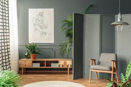 Retro armchair against a gray screen next to a drawing hanging on a dark wall with molding above wooden cupboard in living room interior
