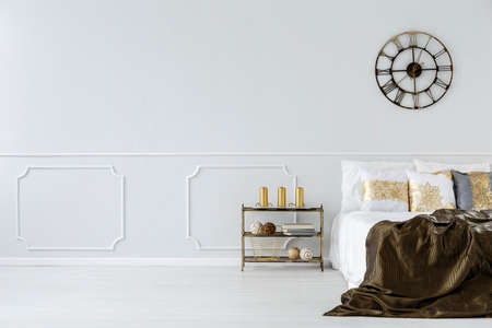 Large bed with golden pillows, bedding and an industrial, metal wall clock in a minimalist bedroom interior with copy space 写真素材