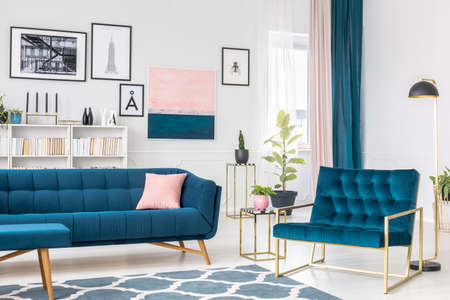 Side angle of blue living room interior with pink and golden accents