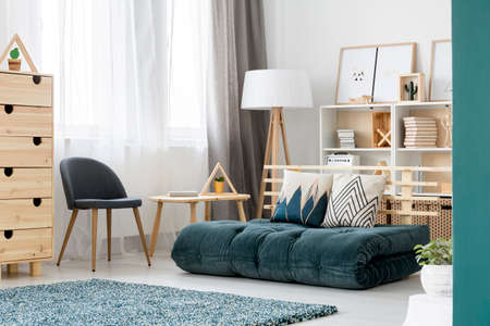 Green mattress, gray chair and wooden table near the window in bright, scandi living room interior 写真素材