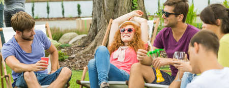 Young happy people chilling and having drinks in the countryside