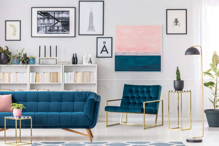 Modern living room interior with blue couch, armchair, golden tables and paintings on the wall Фото со стока