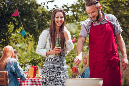 Cheerful young couple standing by a grill, the woman holding a green bottle of beer, the man holding cooking tongs at a summer garden party