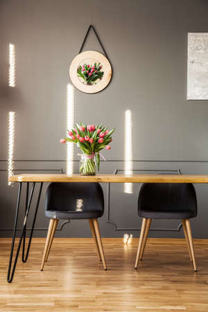 Grey chairs at wooden table with flowers in dining room interior with decor on the wall