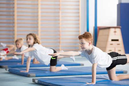 Groep kinderen die gymnastiek op blauwe matten doen tijdens de les lichamelijke opvoeding op school Stockfoto