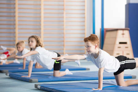 Group of children doing gymnastics on blue mats during physical education class at school Stock Photo