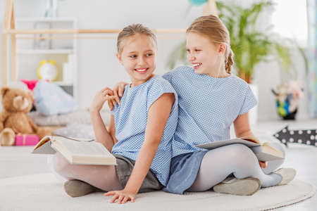 Girl laughing with an arm around her sisters shoulder, sitting on a white rug and reading together