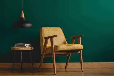 Giallo, poltrona vintage, tavolino con libri e lampada nera impostata sulla parete color smeraldo all'interno del soggiorno